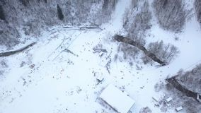 People skiing and snowboarding on snow slope in winter resort. Ski elevator in ski resort in snowy forest aerial view. Drone view winter vacation on luxury ski stock video footage