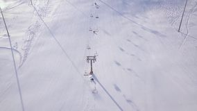 People skiing and snowboarding on snow slope in winter ski resort. Ski elevator on snow mountain drone view. Winter. Activity on ski resort aerial view stock video footage