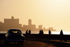 People and skyline of La Habana, Cuba, at sunset. Skyline in La Habana, Cuba, at sunset, with vintage cars on the street and people sitting on the Malecon. Copy Stock Image