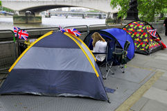 People sleep in a tent. LONDON - JUNE 01: Unidentified people sleep in a tent alongside the River Thames to witness Thames Diamond Jubilee boats parade on June 1 Royalty Free Stock Images