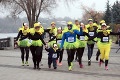 People with a small child in the form of a funny bee run on sports charity Christmas marathon on Dnepropetrovsk street stock images