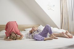 People .small children have fun on their parents` beds, and my mother is trying to sleep for a few more minutes. Small children have fun on their parents` beds Stock Image