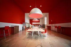People in small cozy cafe. White tables, red chairs and walls Royalty Free Stock Photo