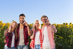 People smart phone call group friends outdoor countryside sunflowers field Stock Photo