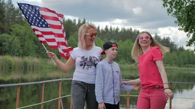 People smiling and waving to camera with US flag stock footage