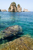 People snorkeling in front of Faraglioni at Scopello on Sicily Royalty Free Stock Image