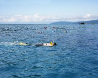 People snorkeling in open blue sea Stock Photos