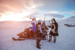 People with snowmobile in desert of frozen north at sunset royalty free stock image