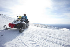 People on snowmobile in winter mountain Royalty Free Stock Image