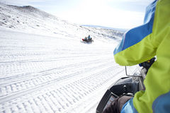 People on snowmobile in winter mountain Stock Photography