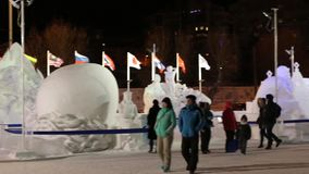 People at snowy sculptures in Ice Town at night stock video footage