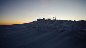 People on the snowy summit. People on the snowy hill at sunset, winter Stock Photo