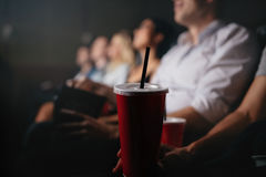 People with soft drinks in movie theater Stock Image