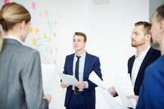 People speaking at a meeting. Young business people with reports speaking at a meeting at office Royalty Free Stock Photos