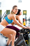 People Spinning in the gym on bicycles Royalty Free Stock Photos