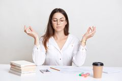 People and spirituality concept. Relaxed brunette young woman poses at workplace in mudra sign, enjoys peaceful atmosphere, pull h. Erself together and prepares royalty free stock photo