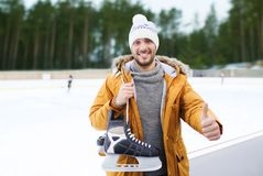 Man showing thumbs up on outdoor skating rink. People, sport, gesture and leisure concept - happy young man with ice-skates showing thumbs up on skating rink Royalty Free Stock Images