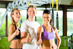 People in sport gym on suspension trainer Royalty Free Stock Images