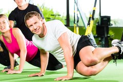 People in sport gym on suspension trainer Stock Photos