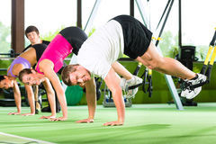 People in sport gym on suspension trainer Royalty Free Stock Image