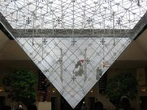 People that sportingly wash the inverted  pyramid of the Louvre from inside  to Paris. France. Glass piramide. Piramide of the Louvre of Paris in France Royalty Free Stock Photography