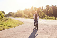 People, sports and healthy active lifestyle concept. Smiling hipster schoolboy with trendy hairdo riding bicycle outdoors. Young c. Yclist having vacations Royalty Free Stock Images
