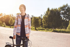 People, sports, leisure and active healthy lifestyle. Portrait of young hipster bicyclist wearing shirt standing near his bike whi Royalty Free Stock Photo