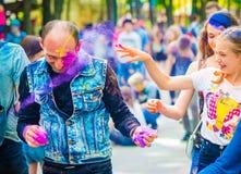People sprinkle colorful paints during celebrating holi fest. Khakiv, Ukraine - 19 May 2018: People sprinkle colorful paints during the festival. People with royalty free stock image