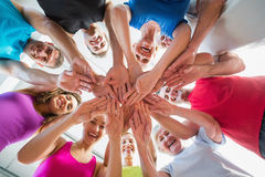 People stacking hands at health club. Low angle view of fit people stacking hands at health club Stock Photos