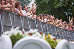 People stand and applaud at fence at concert Stock Photos