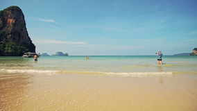 People Stand in Azure Sea Foamy Waves Photo. Backside view distant people stand in shallow azure sea foamy waves photo against Thai boats blue sky stock video footage