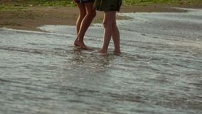 People stand with bare feet in the water at the beach stock footage