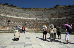People stand at the base of the Roman theatre ruins at the ancient site of Ephesus in Turkey. People stand at the base of the Roman theatre ruins at the ancient Stock Photography