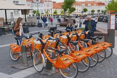 People stand at the bicycle rental point at the City Hall square in Vilnius, Lithuania. Royalty Free Stock Photos