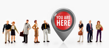 People stand in front the sign you are here. Miniature people  - people stand in front the sign you are here Royalty Free Stock Photo