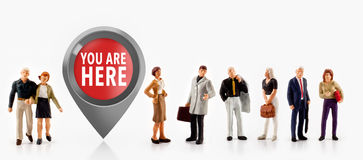 People stand in front the sign you are here. Miniature people  - people stand in front the sign you are here Royalty Free Stock Photos