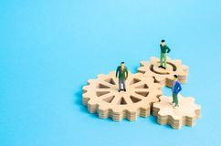 People stand on gears. Concept of business ideas and investments, cooperation and teamwork with business partners and employees. Business development, success stock photography