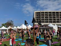 People stand with hands on heart and stomach during outdoor yoga. North Shore, Oahu - March 1, 2018: People stand with hands on heart and stomach during outdoor Stock Photos