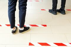 Free People Stand In Line Keeping Social Distance, Standing Behind A Warning Line During Covid 19 Coronavirus Quarantine. Safe Shopping Royalty Free Stock Image - 182656746