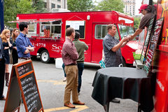 People Stand In Line To Order Meals From Food Truck Stock Photos