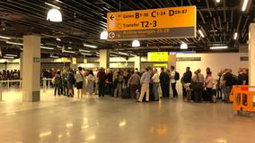 People stand in line waiting for departure at the airport terminal stock footage