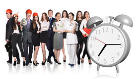 People stand near alarm clock Royalty Free Stock Image