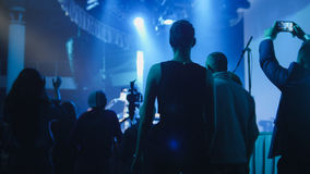 People stand near the stage during a concert. Absract blurred Young people stand near the stage during a concert at the club stock photos