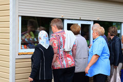 People stand in a queue at the kiosk for the sale of vegetables Royalty Free Stock Photos