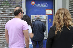People stand in a queue to use the ATMs of a bank Royalty Free Stock Image