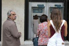 People stand in a queue to use the ATMs of a bank Stock Photos