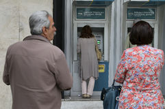 People stand in a queue to use the ATMs of a bank Stock Images