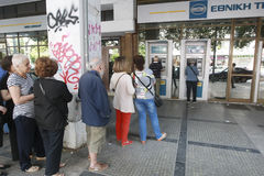 People stand in a queue to use the ATMs of a bank Royalty Free Stock Photo