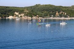 People on stand up paddle board and parasailing Valtos beach Parga. Greece royalty free stock image
