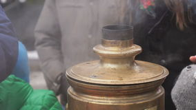 People standing around russian boiling samovar stock video footage